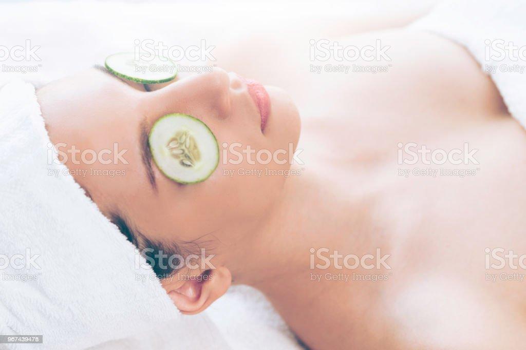 Frau bekommen Natur Augenbehandlung von Gurke. – Foto