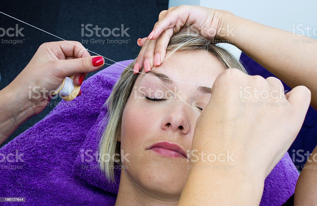 Woman getting eyebrow threaded  stock photo