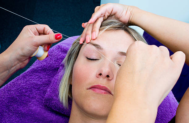 Woman getting eyebrow threaded  beautician makes threading hair removal procedure to blond woman in salon threading stock pictures, royalty-free photos & images