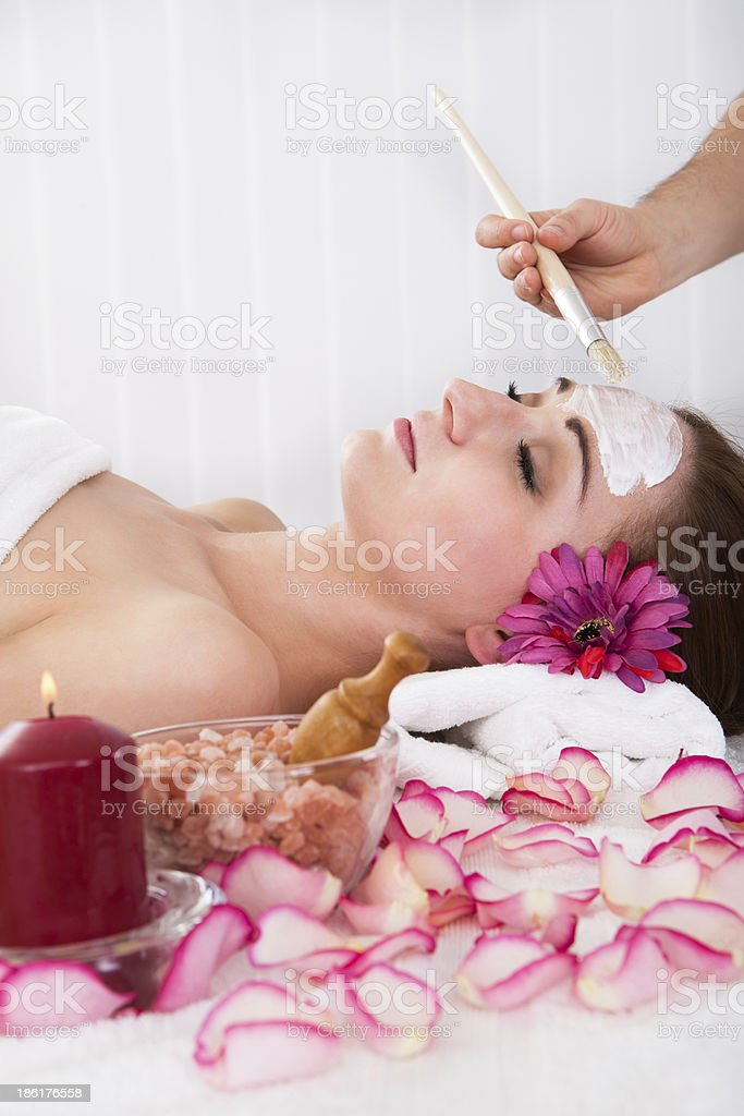 Woman getting facial mask at spa studio royalty-free stock photo