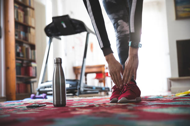 Woman getting fit and doing home training in the living room stock photo