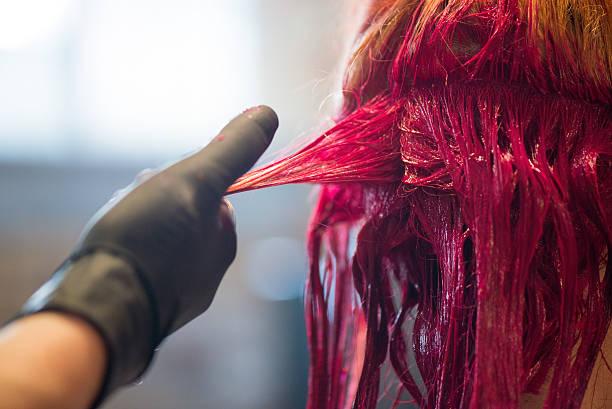 woman getting hair dyed red - gekleurd haar stockfoto's en -beelden