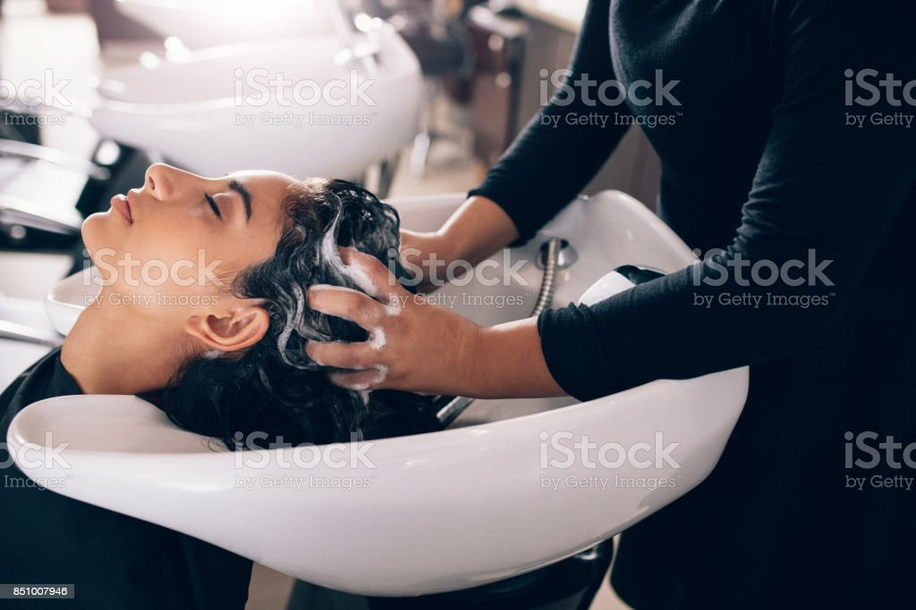 Woman getting hair shampooed at salon stock photo