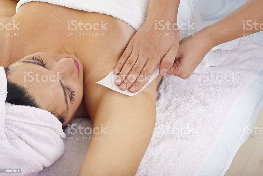 Woman getting her armpit waxed stock photo