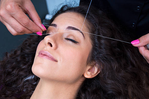 A woman getting her eyebrows threaded attractive woman in beauty salon on facial hair removal eyebrow threading procedure threading stock pictures, royalty-free photos & images