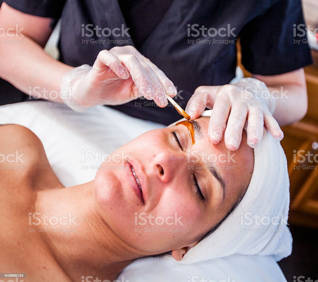 Woman Getting Her Eyebrows Waxed stock photo