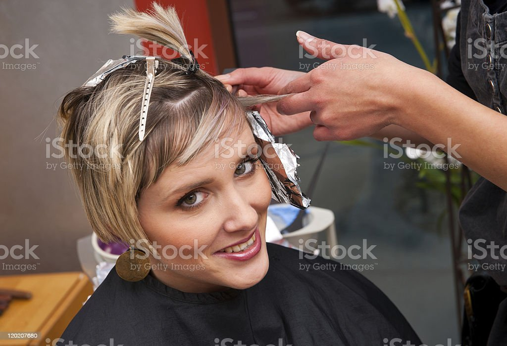 A woman getting her hair dyed at a salon royalty-free stock photo