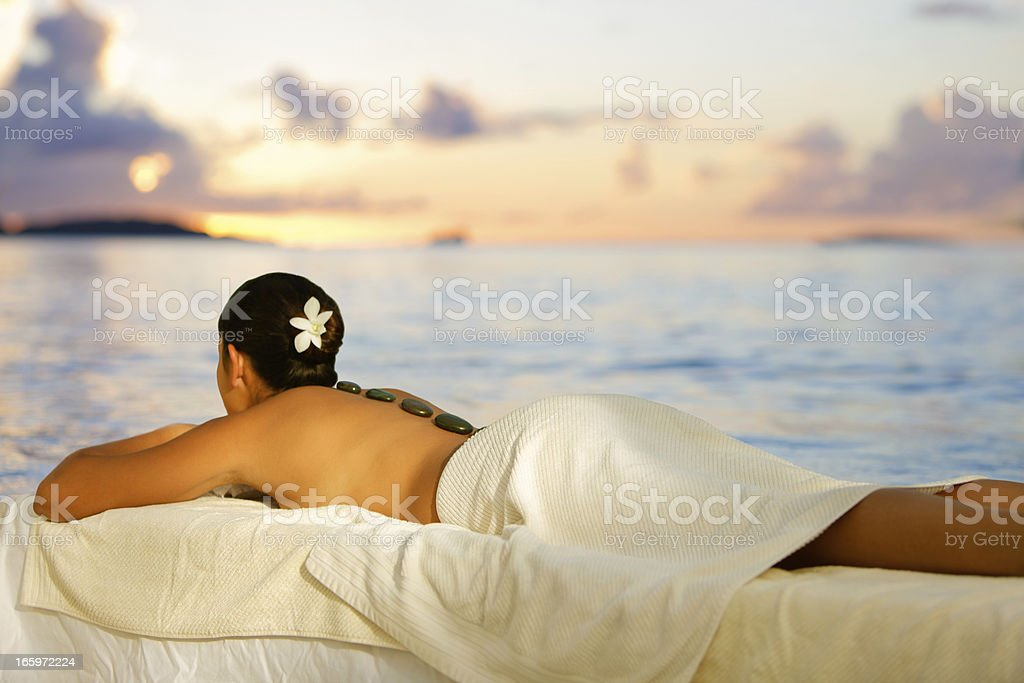 woman getting hot stone massage at sunset on the beach stock photo