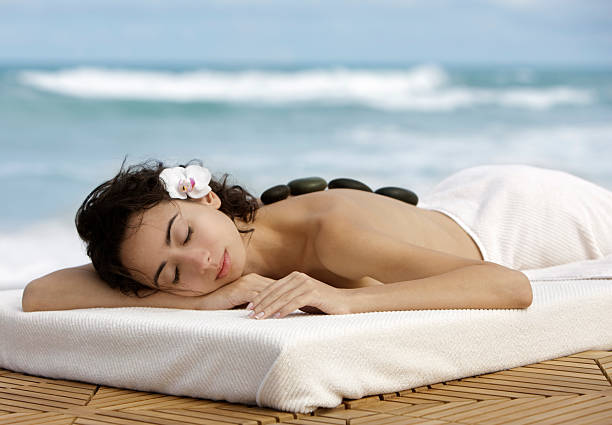 woman getting hot stone massage at the beach stock photo