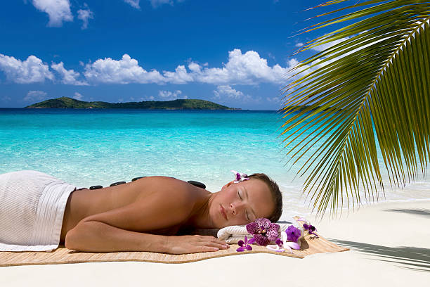 woman getting hot stone massage on the Caribbean beach stock photo