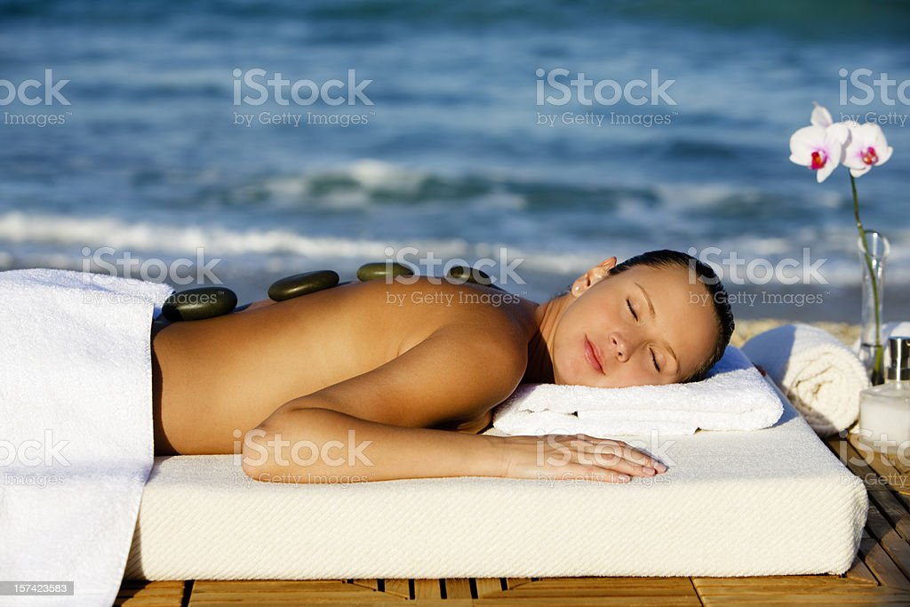 woman getting hot stone spa massage stock photo