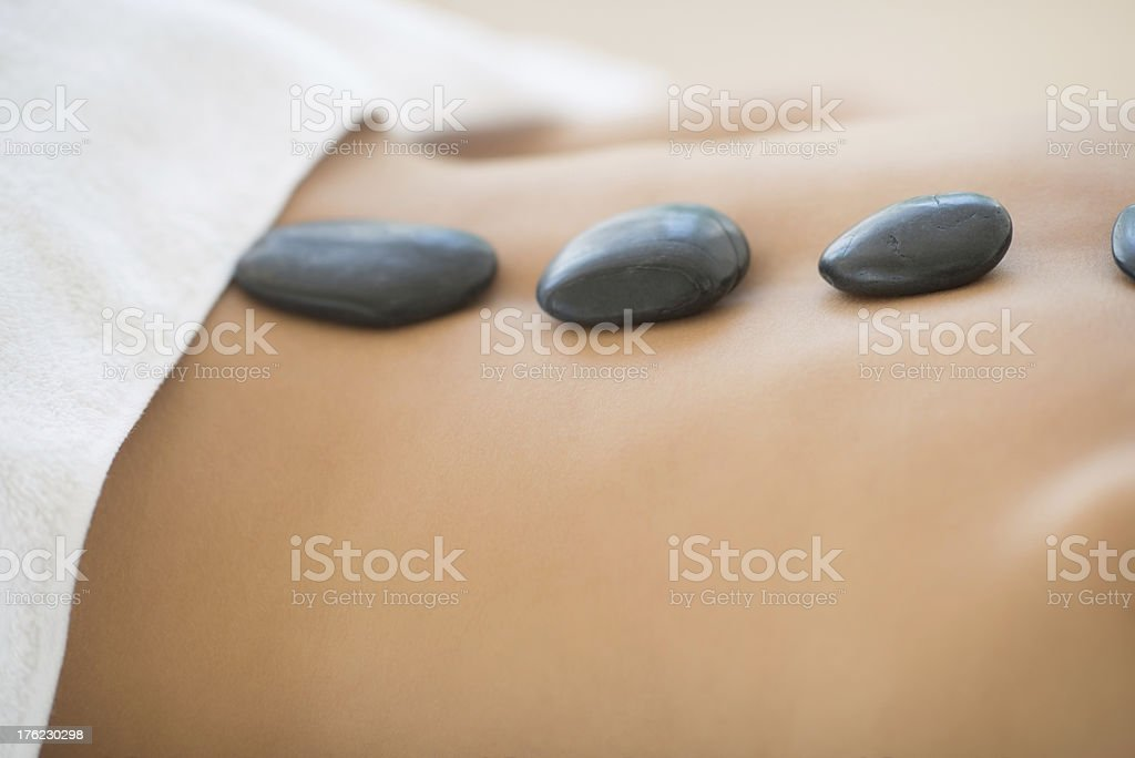 Woman Getting Hot Stone Therapy At Spa stock photo