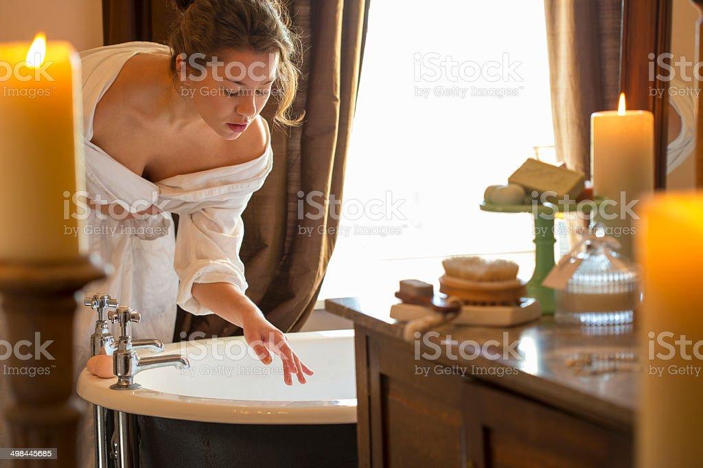 Woman Getting in the Bath stock photo