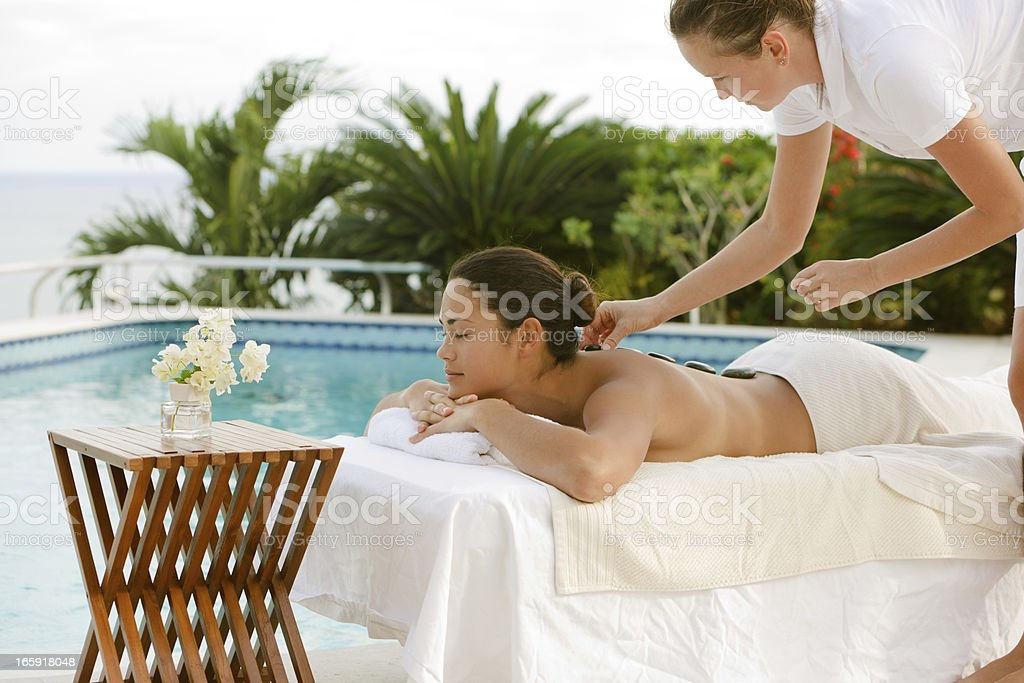 young woman getting lastone treatment by a masseuse at luxury spa...