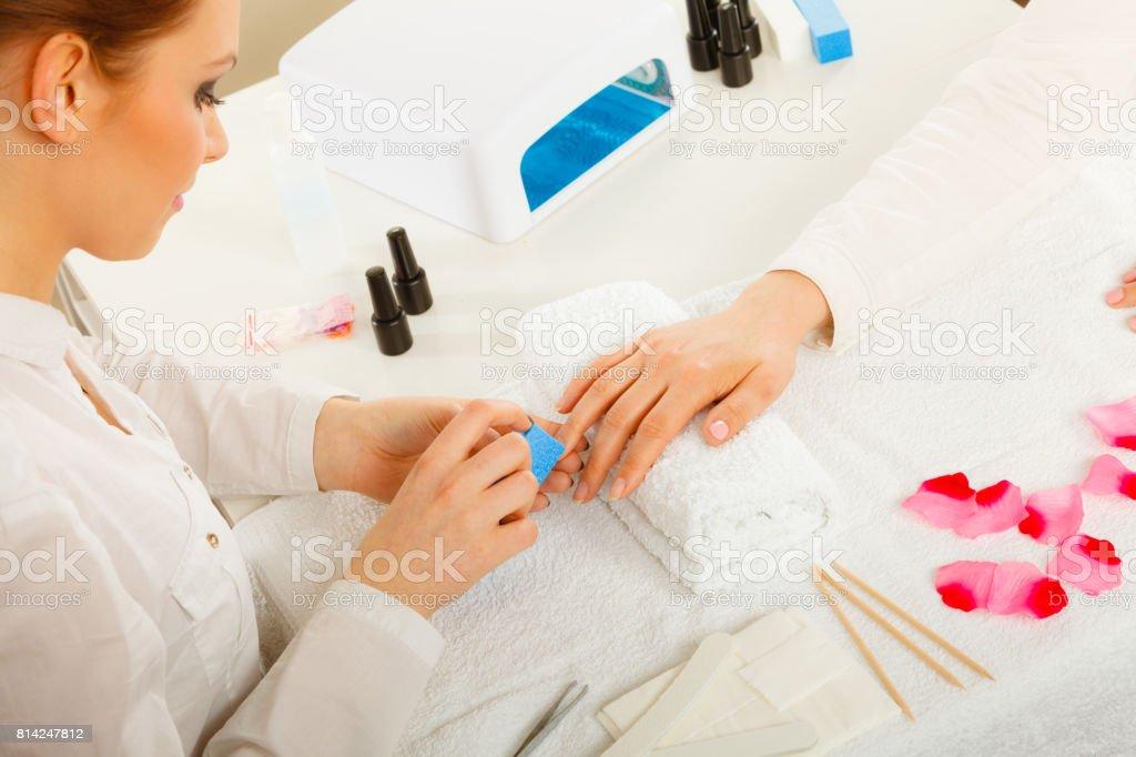 Woman hand on towel, beautician file nails. Beauty wellness spa...