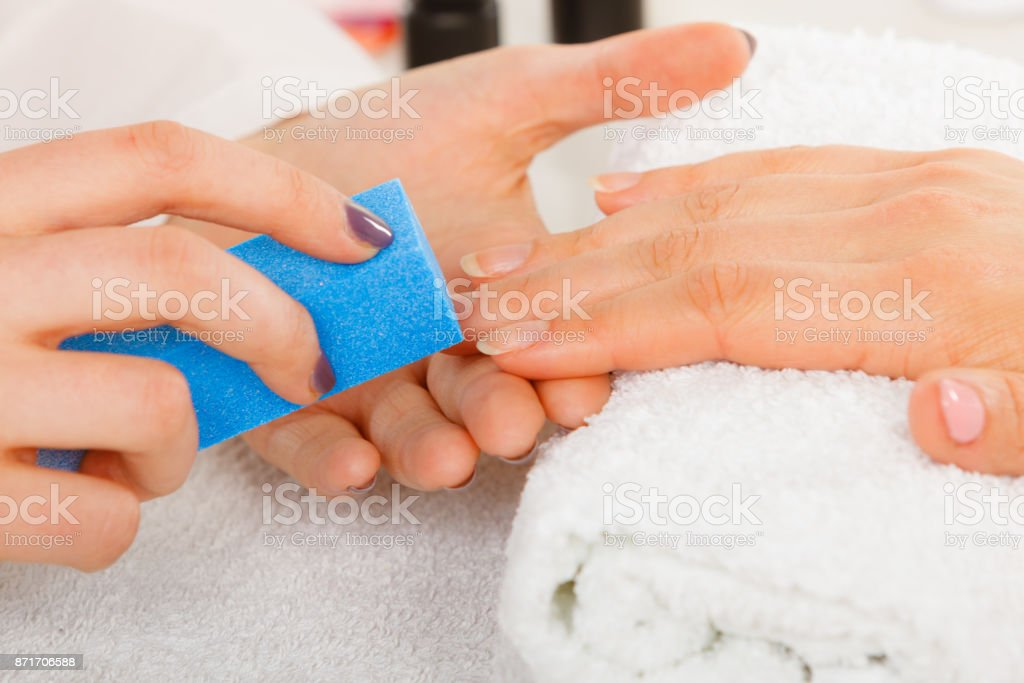 Woman getting manicure done file nails stock photo