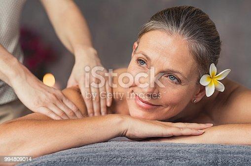 Senior woman in spa salon getting massage. Closeup of a beautiful woman during spa treatment. Beautiful mature woman receiving massage of shoulder at beauty salon.