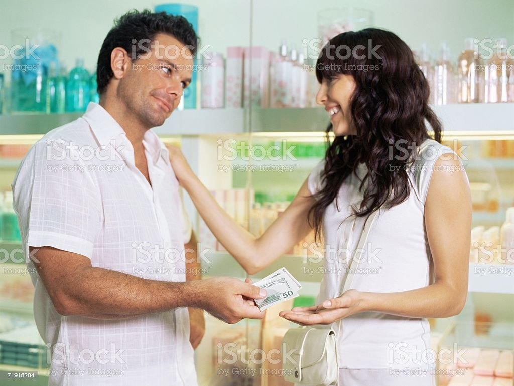 Woman getting money from husband royalty-free stock photo