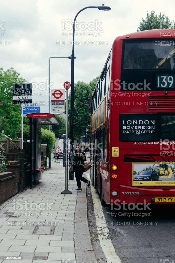 Woman getting off a doubledecker bus stock photo