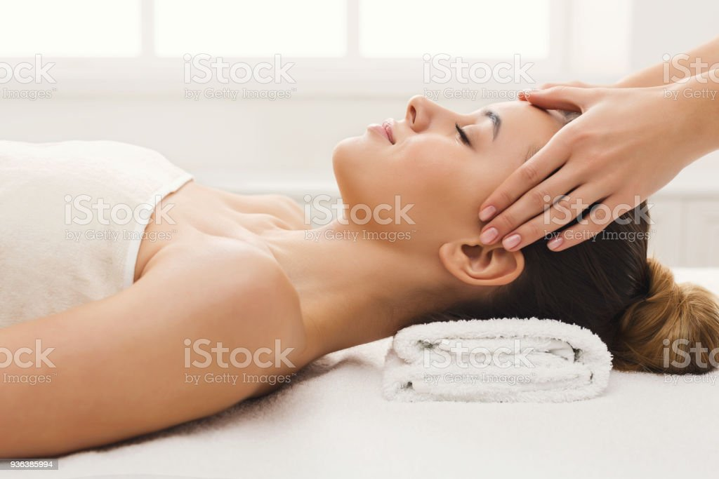 Woman getting professional facial massage at spa salon stock photo