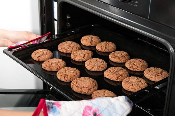 frau zu in der pfanne schmoren mit hafer-cookies aus dem ofen - schokolade gebratene kuchen stock-fotos und bilder