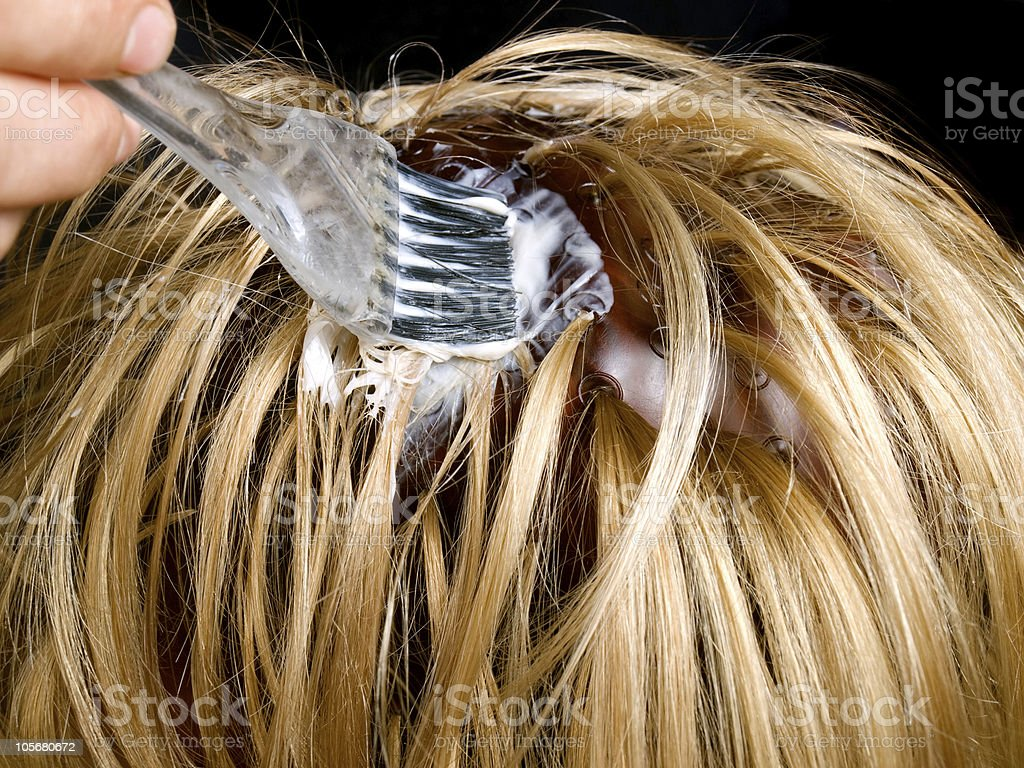 Woman getting roots of hair dyed royalty-free stock photo