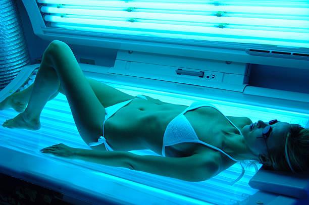 woman getting solarium beauty treatment - gebruind stockfoto's en -beelden