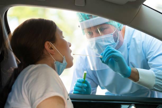 Woman getting tested at a coronavirus drive thru station stock photo