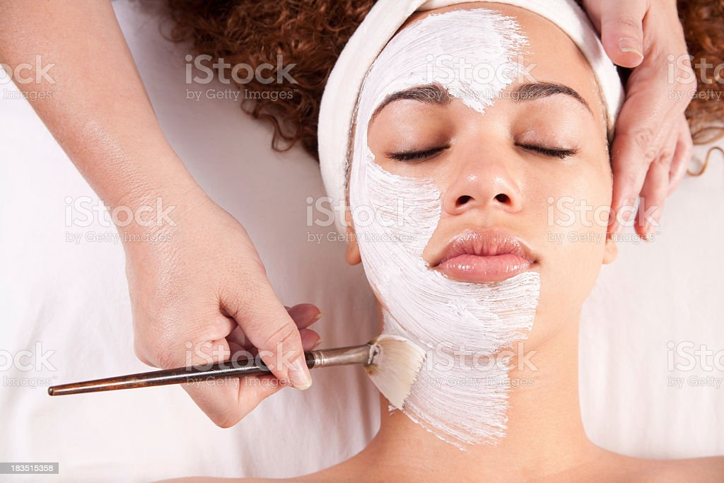 Woman getting white mud painted on her face stock photo