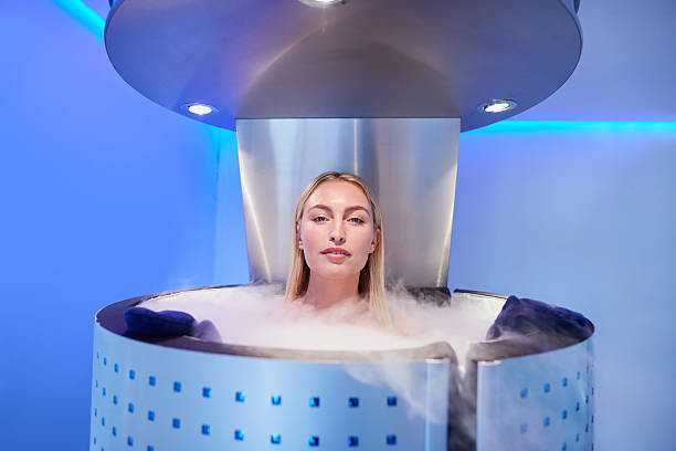 Woman getting whole body cryotherapy Woman in cryosauna booth for whole body cryotherapy. Caucasian female in freezing chamber with nitrogen vapors. cryotherapy stock pictures, royalty-free photos & images