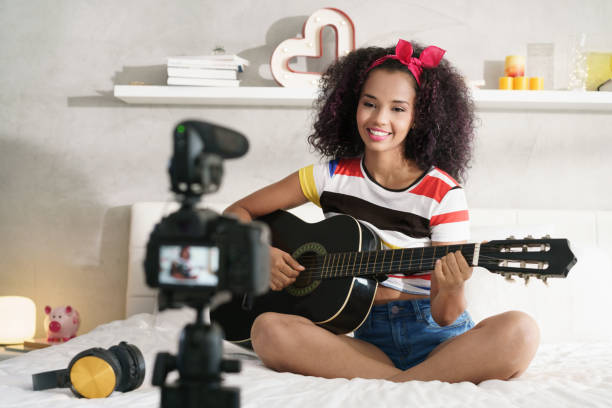 frau girving gitarre klasse internet mit video-tutorial - one song training stock-fotos und bilder