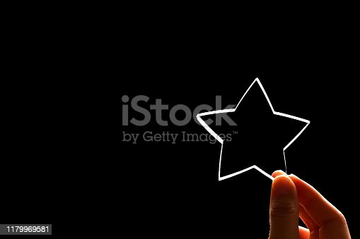 A woman gives a star. The concept of a positive rating, reviews and feedback on black background.