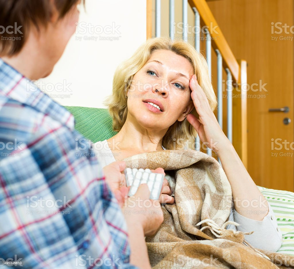 woman  gives her friend a sleeping pill stock photo