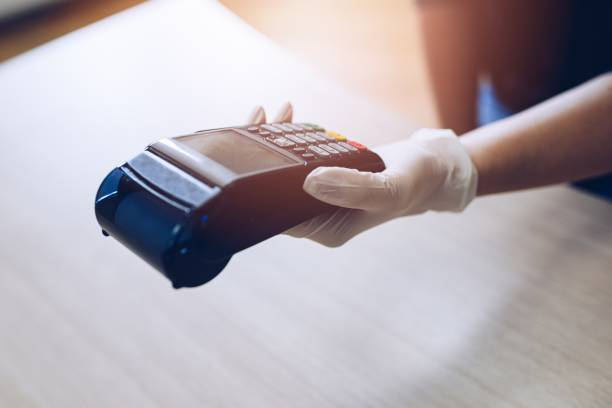 Woman gives the terminal for non-contact card payment.She wears protective gloves. stock photo