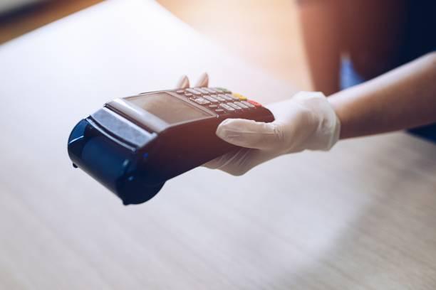 Frau gibt das Terminal für kontaktlose Kartenzahlung. Sie trägt Schutzhandschuhe. – Foto