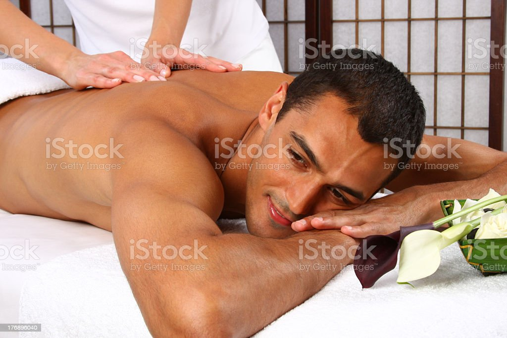 Woman giving a back massage to a dark haired man stock photo