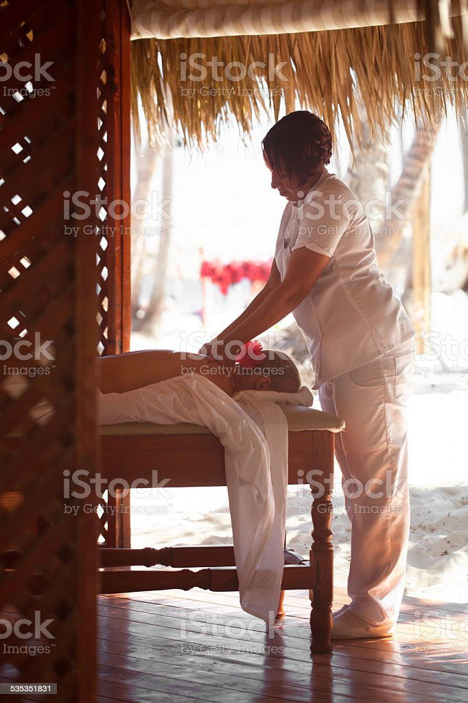 Woman giving a female customer body massage stock photo