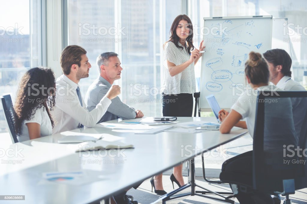 Woman giving a presentation to her team. stock photo