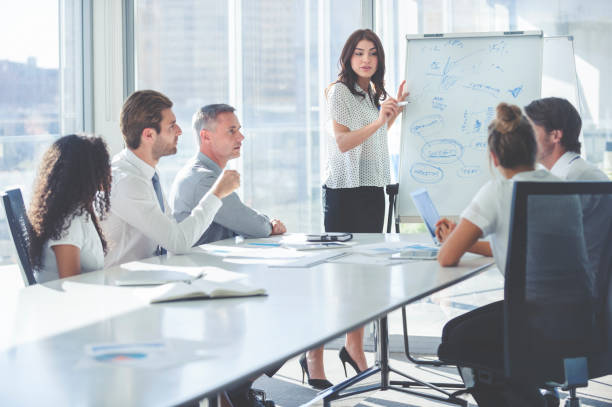 woman giving a presentation to her team. - teaching stock photos and pictures