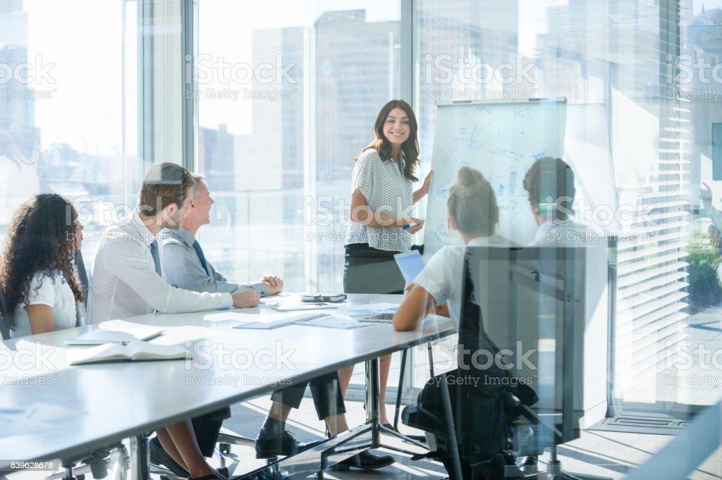 Frau hält einen Vortrag zu ihrem Team. Lizenzfreies stock-foto