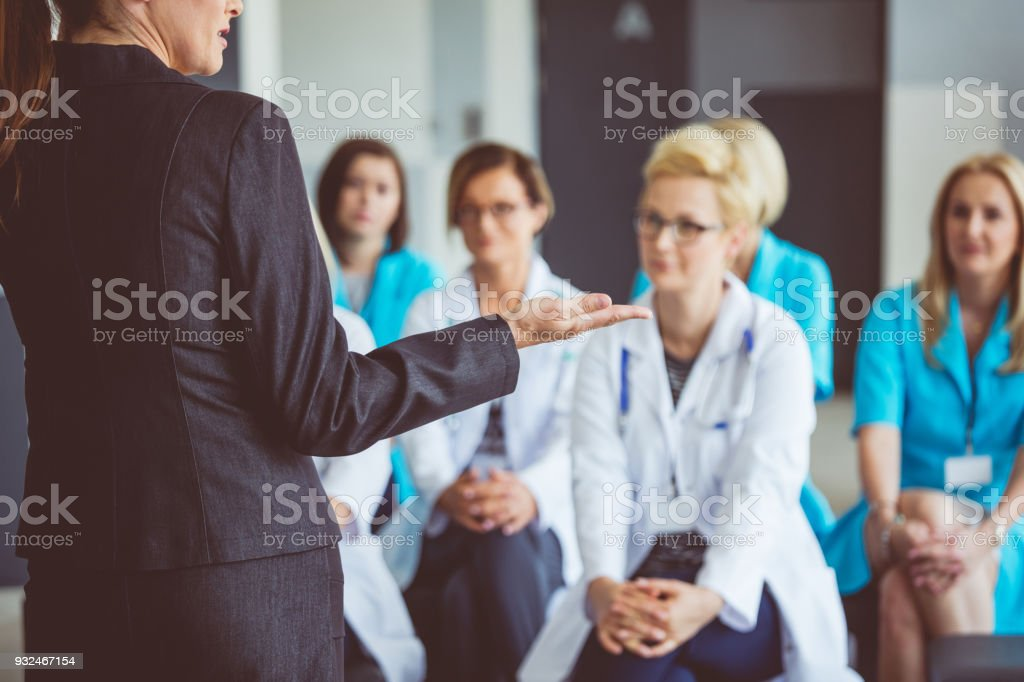 Woman giving a speech on seminar for doctors stock photo