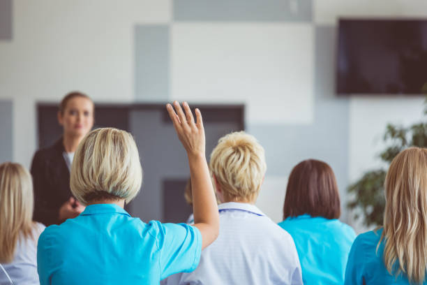 Woman giving a speech on seminar for medical staff Woman giving a speech on seminar for doctors. Focus on female doctor raising hand. debate stock pictures, royalty-free photos & images
