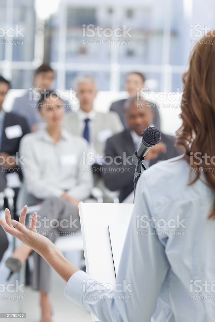 Woman giving a speech to the seated business team stock photo