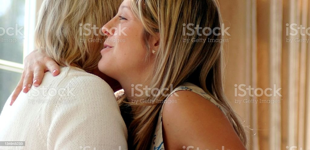 Woman Giving Another Lady a Hug stock photo
