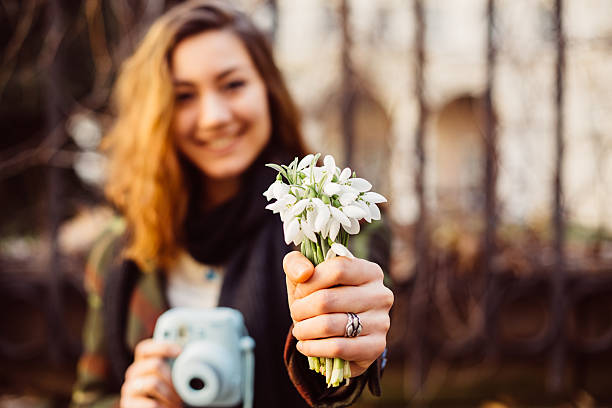 woman giving bouquet of snowdrops - snowdrop stock pictures, royalty-free photos & images