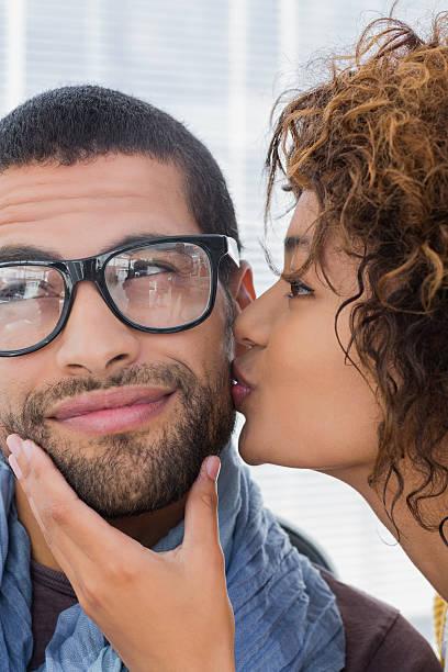 woman giving boyfriend kiss on the cheek - brunette woman eyeglasses kiss man foto e immagini stock