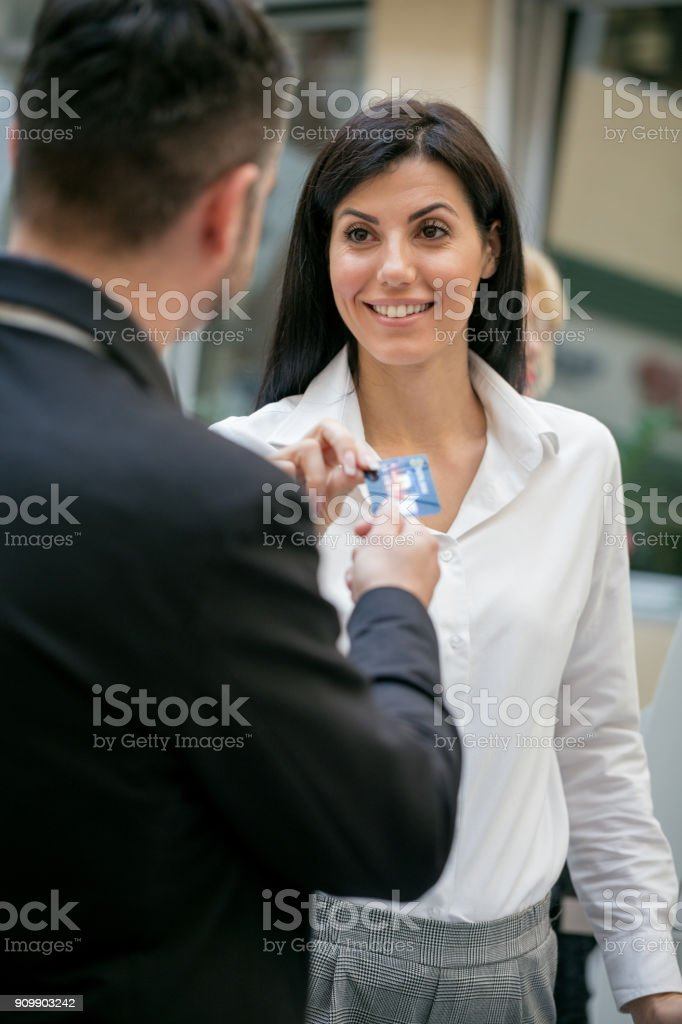 Woman giving credit card to man stock photo