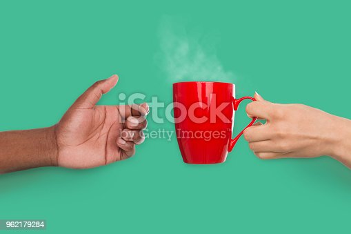 Woman giving cup of hot coffee her african-american boyfriend on turquoise background, family care and support