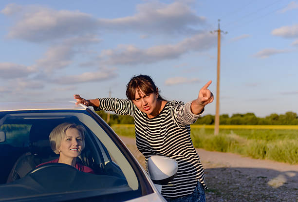 Woman giving directions to a lost driver Woman giving directions to a lost woman driver on a rural road pointing in the direction she should drive stranger stock pictures, royalty-free photos & images