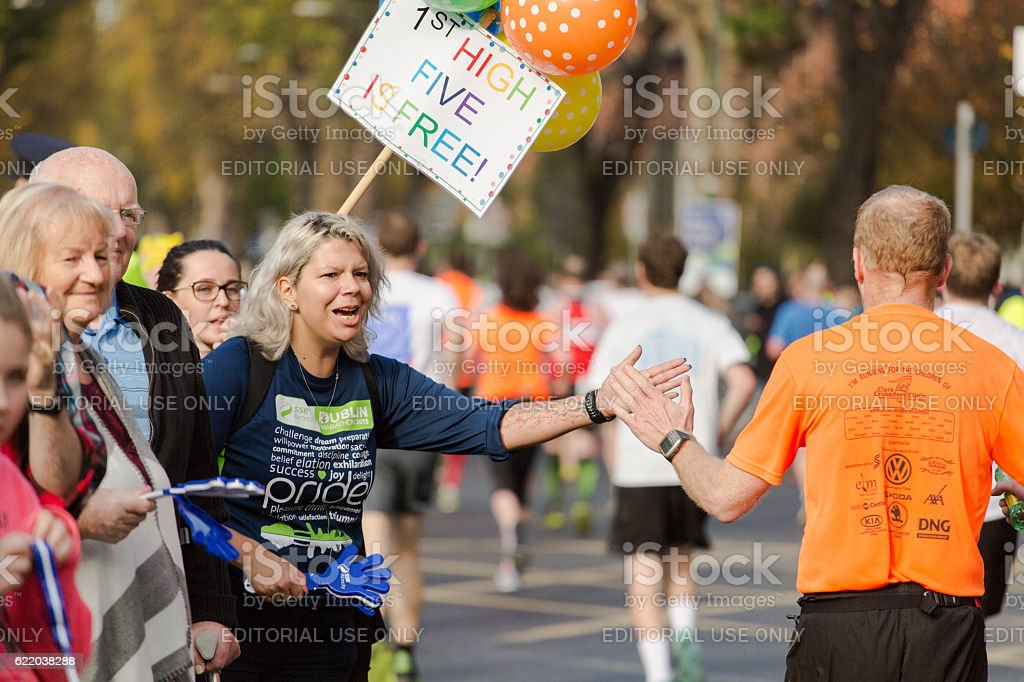 Woman giving highfives to runners stock photo